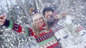 Smiling blond woman and handsome young man taking photo of themselves in snowy forest stock footage