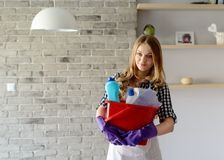 Smiling  blond woman holding a bucket full of cleaners Stock Photography