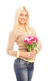 A smiling blond woman holding a bunch of flowers Stock Photography