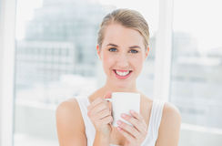 Smiling blond woman holding cup of coffee Royalty Free Stock Photos