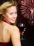 Smiling blond woman holding wine and celebrating Stock Photography