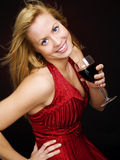 Smiling blond woman holding wine and celebrating Stock Photo