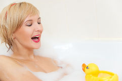 Smiling blond woman lying in bubble bath Royalty Free Stock Photography
