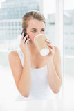 Smiling blond woman on the phone drinking coffee Royalty Free Stock Image