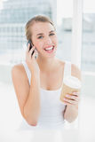 Smiling blond woman on the phone holding coffee Royalty Free Stock Photography