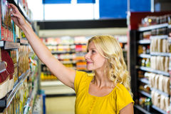 Smiling blond woman picking product on shelf Royalty Free Stock Images