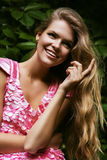 Smiling blond woman in pink dress. In forest Stock Photos