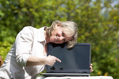 Smiling blond woman pointing at laptop. A smiling beautiful mature blond woman sitting in her garden presenting her laptop and pointing at it Stock Photos