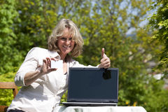 Smiling blond woman posing thumbs up. A smiling beautiful mature blond woman sitting in her garden presenting her laptop and a business card with copy space and Royalty Free Stock Photos