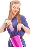 Blond woman put in card into bag. Smiling blond woman put in card into bag over white backround Stock Photo