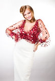 Smiling blond woman in red blouse and white skirt Royalty Free Stock Photos