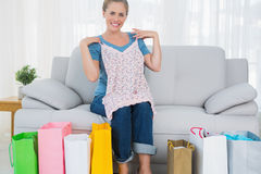Smiling blond woman with shopping bags trying out a top Stock Photos