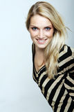 Smiling blond woman in a striped top. Attractive smiling blond woman in a stylish striped top leaning forward into the frame from the right and looking up at the Royalty Free Stock Images