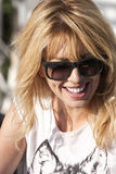 Smiling blond woman with sunglasses. A woman with sunglasses is smiling happily. She is wearing a white T-shirt. The scene takes place during the day under a hot Royalty Free Stock Image