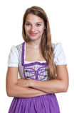 Smiling blond woman in a traditional purple dress Royalty Free Stock Images