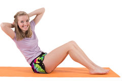 Smiling blond woman training stomach muscles on a mat. Royalty Free Stock Image