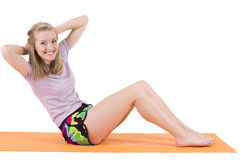 Smiling blond woman training stomach muscles on a mat Royalty Free Stock Photos