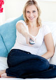 Smiling blond woman watching TV. Sitting on sofa at home stock photography