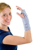 Smiling Blond Woman Wearing Supportive Wrist Brace. Waist Up Portrait of Smiling Young Blond Woman Looking at Camera and Wearing Supportive Wrist Brace in Studio Royalty Free Stock Photo
