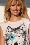 Smiling blond woman with wolf t-shirt. A woman with sunglasses is smiling happily. She is wearing a white T-shirt with a wolf drawn. The scene takes place Stock Photo