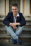 Smiling blond young man sitting on stone stair steps outside Royalty Free Stock Images