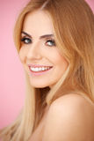 Smiling blond young woman over pink Stock Photography