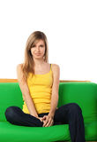 Smiling blond young woman on sofa Stock Photos