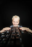 Smiling blond youth holds keyboard in both hands Stock Photos