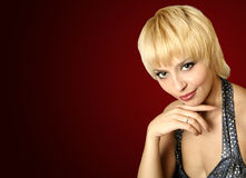 Smiling blonde. The smiling blonde on a dark background Stock Photography