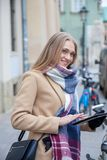 Smiling blonde beautiful woman holding tablet on city street. royalty free stock image