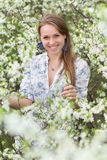 Smiling blonde in blooming garden Royalty Free Stock Photography