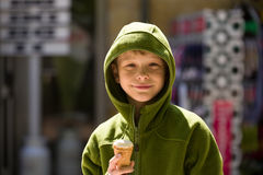 Smiling blonde boy in green sweater with ice cream. Royalty Free Stock Photo