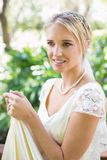 Smiling blonde bride holding her dress Stock Photo