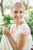 Smiling blonde bride holding her dress looking at camera Royalty Free Stock Images