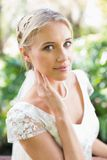 Smiling blonde bride in pearl necklace touching her face Royalty Free Stock Photo