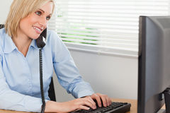 Smiling blonde businesswoman phoning and typing Royalty Free Stock Images