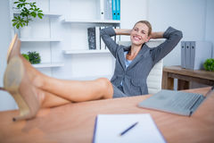 Smiling blonde businesswoman relaxing herself Royalty Free Stock Photos