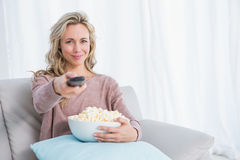Smiling blonde changing tv channel while eating popcorn Stock Photography