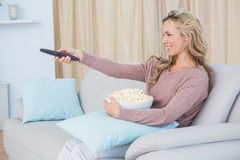 Smiling blonde changing tv channel while eating popcorn Royalty Free Stock Images