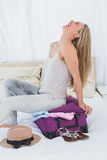 Smiling blonde closing baggage sitting on it Royalty Free Stock Images