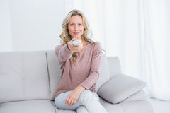 Smiling blonde on couch changing tv channel Royalty Free Stock Images