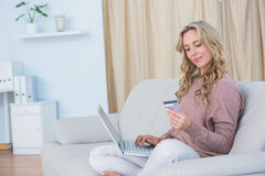 Smiling blonde on couch using laptop and credit card Royalty Free Stock Image