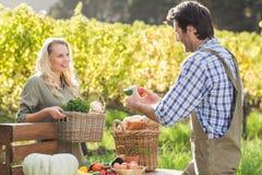 Smiling blonde customer buying vegetables Stock Image