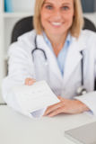 Smiling blonde doctor giving prescription looks Royalty Free Stock Images