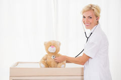 Smiling blonde doctor with stethoscope in the teddy bear Royalty Free Stock Photo