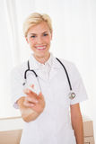 Smiling blonde doctor with syringe and stethoscope Stock Photography