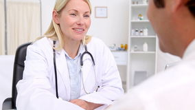 Smiling blonde doctor talking to her patient stock video footage