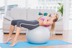 Smiling blonde doing sit ups with exercise ball holding dumbbells Stock Images