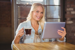 Smiling blonde drinking coffee and holding tablet Royalty Free Stock Image