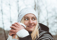 Smiling  blonde drinking coffee outdoors Royalty Free Stock Photos